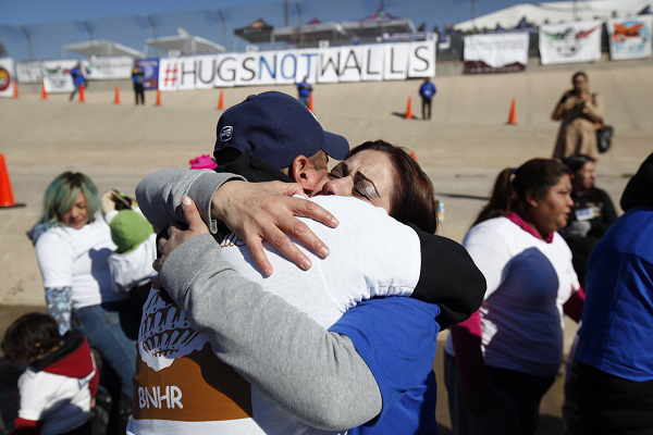 Family members hug at the US-Mexico border