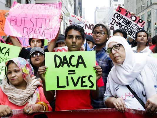 Photo of protestors at a Save DACA rally. One with a sign that reads DACA = Lives.