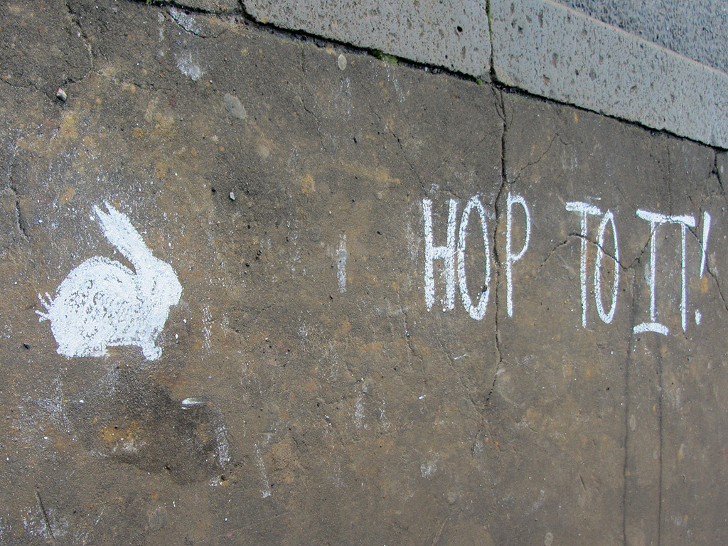 "A graffiti image of a rabbit and the words ""hop to it!"""