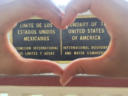 A person places their hands in the shape of a heart over a sign at the US-Mexico border
