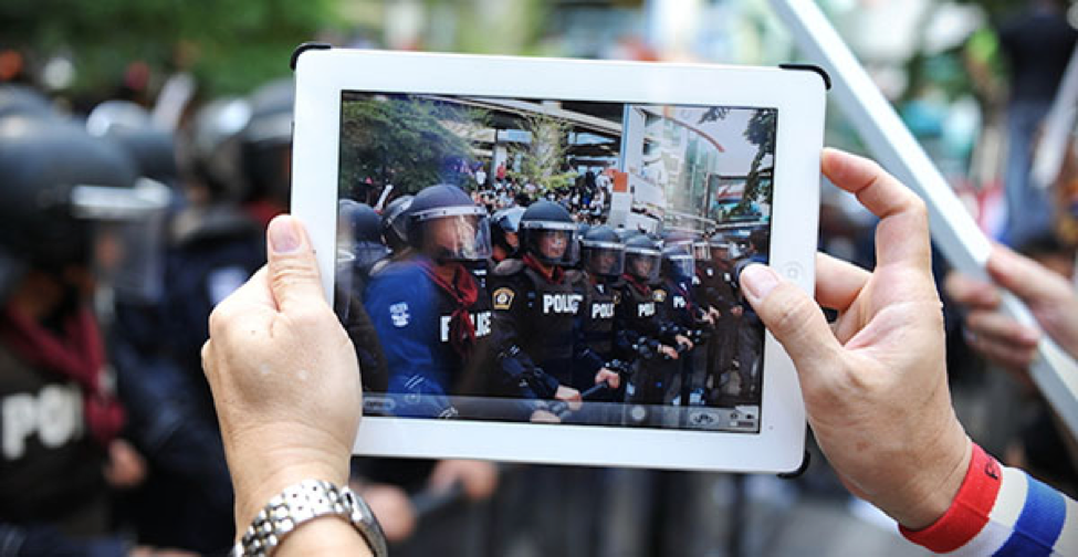 Photograph of someone holding an i-Pad filming a group of uniformed police officers