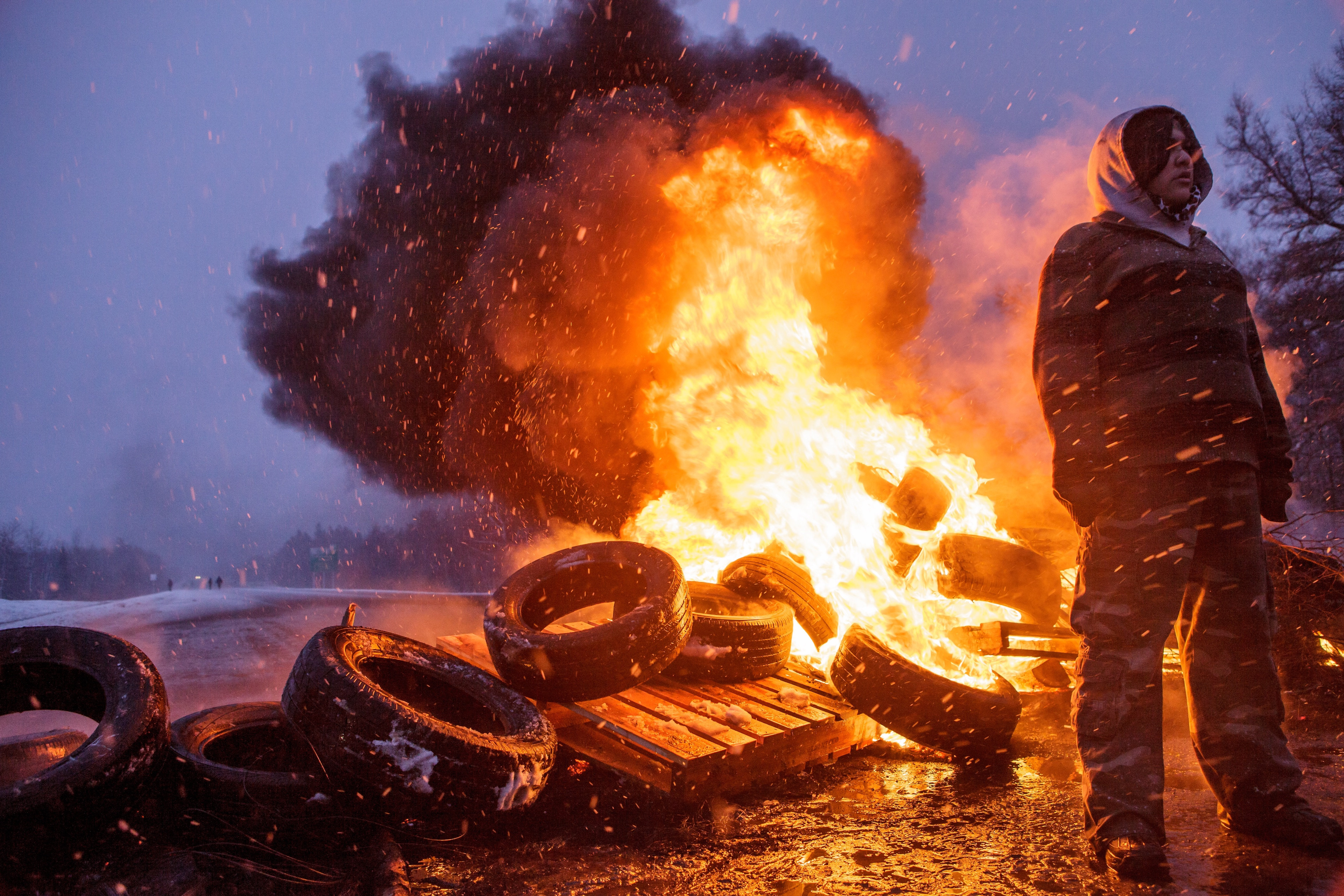 Photo of a person standing in front of burning tires in the documentary Water Warriors