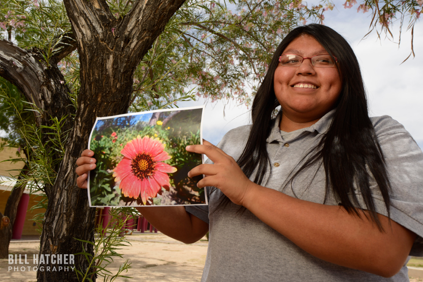 Photo by: Bill Hatcher. A girl of the Tohono O'odham Nation in Sells, Arizona, shows a photograph of local flora.