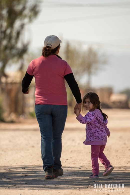 Photo by Bill Hatcher. A mother and her daughter take a walk in their hometown near the border.