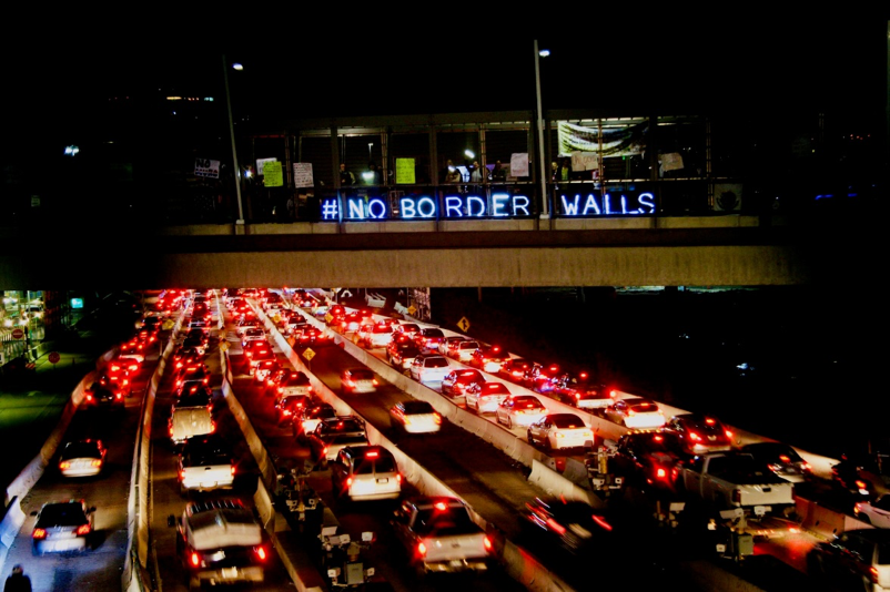 Photo by Pedro Ruiz. In January 2017, following Trump's election, the Overpass Light Brigade joined border community members to send a message over southbound lanes to Tijuana.