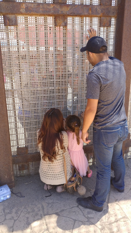 Photo by: Osvaldo Ruiz, Border Angels. A couple and their child talks to family on the other side of the border at Friendship Park in San Diego.