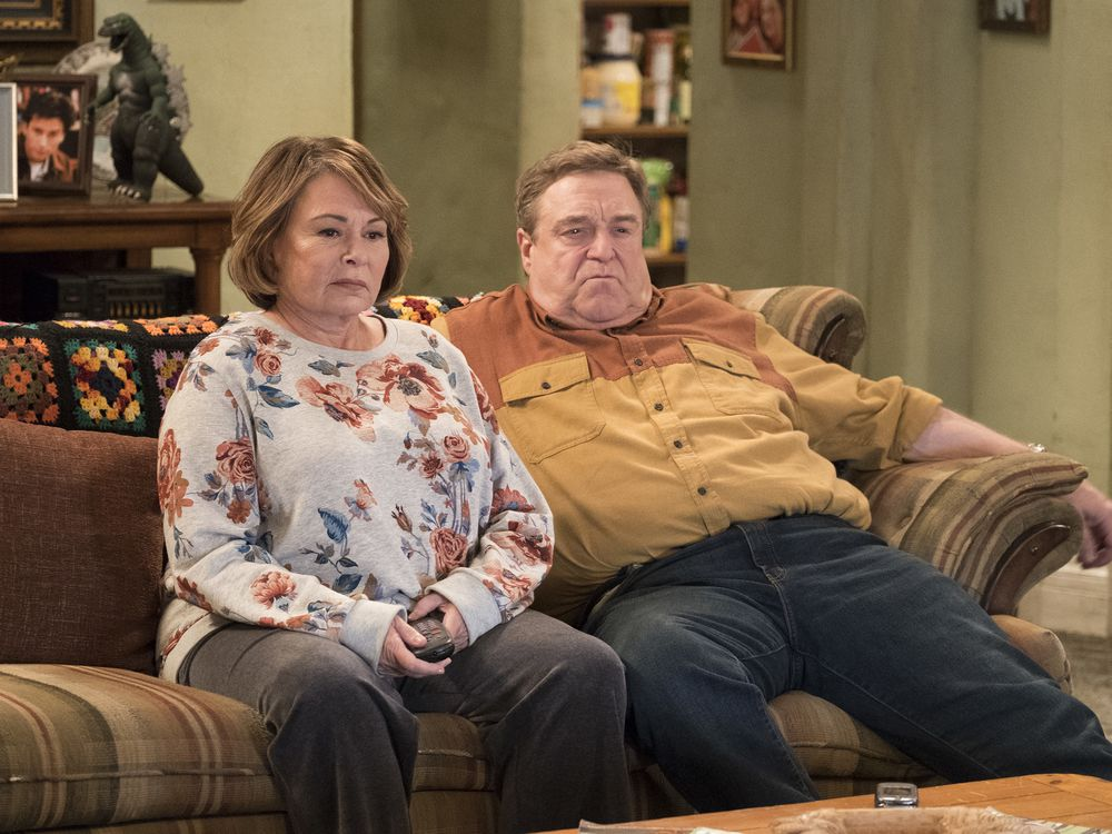 A still from the Roseanne reboot tv show with Roseanne Barr and John Goodman sitting on their couch